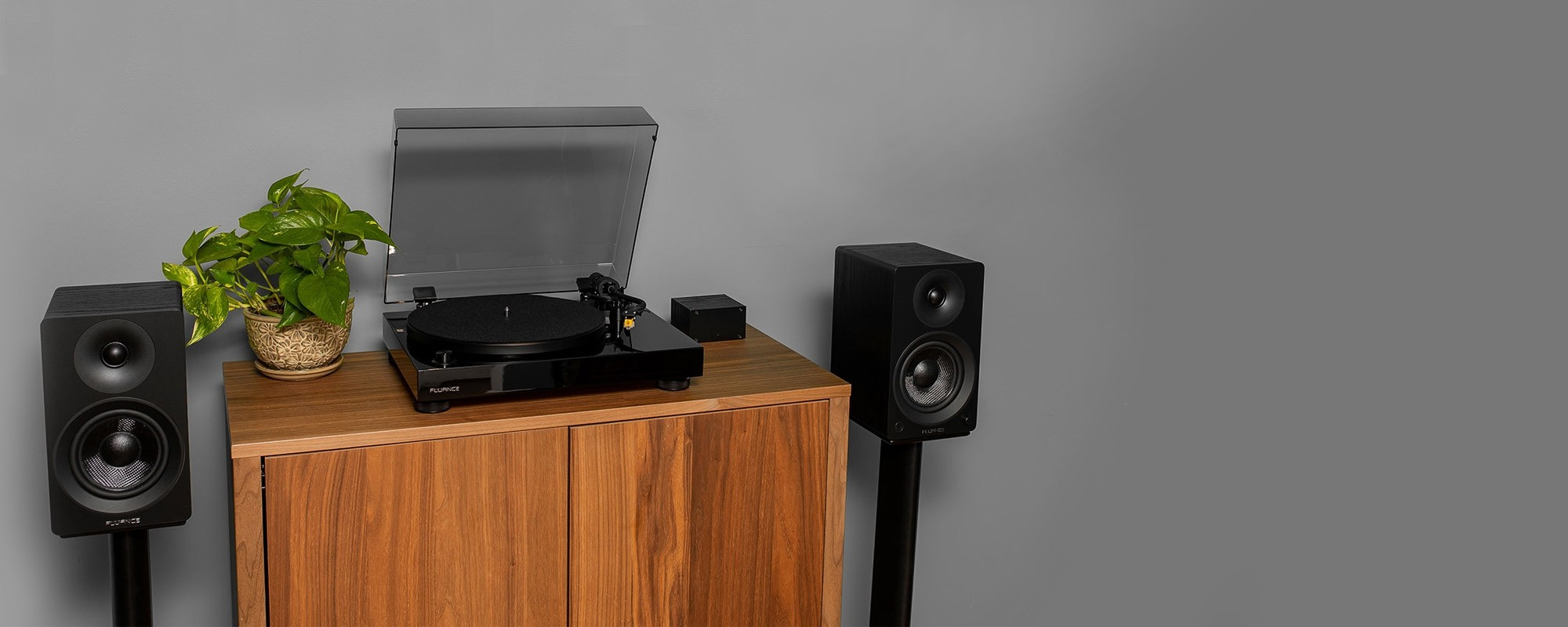 "Classic High Fidelity Vinyl Turntable with Ai40 5"" Powered Bookshelf Speakers - on cabinet with plant 2"