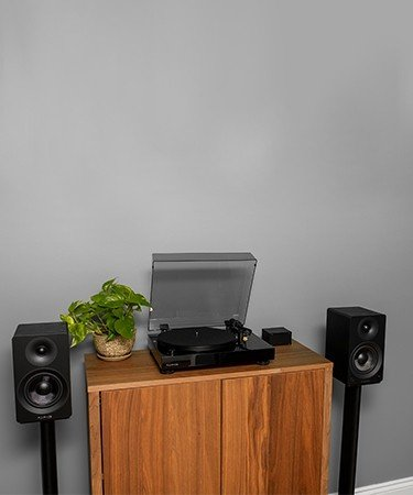 "Classic High Fidelity Vinyl Turntable with Ai40 5"" Powered Bookshelf Speakers - on cabinet with plant"